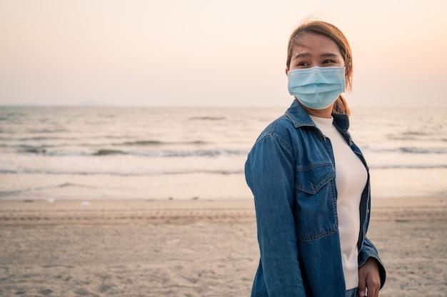 Covid-19コンセプト、ビーチで夕日と屋外の彼女の顔に衛生防護マスクを着ているアジアの若い女性