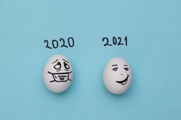 코비드-19 개념입니다. 파란색 배경에 손으로 그린 얼굴이 있는 계란. 2020년 대 2021년