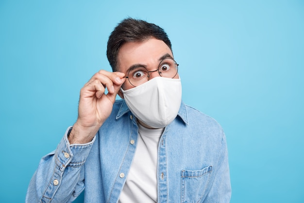 Concetto covid19. un uomo adulto serio e attento guarda attraverso gli occhiali indossa una maschera protettiva e chiede di seguire le regole di allontanamento sociale vestito con una camicia di jeans