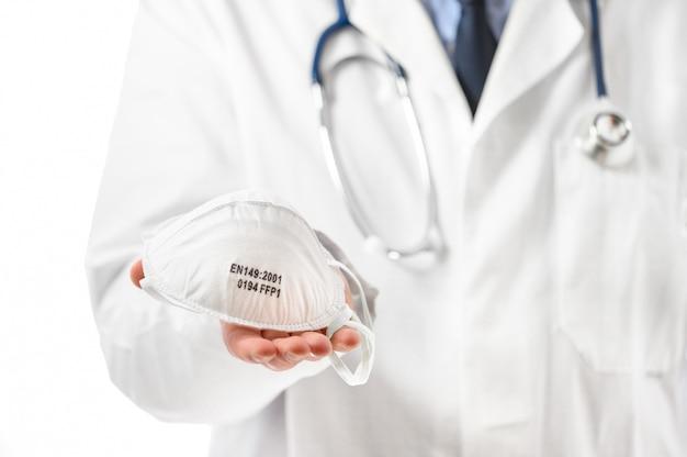 Концепция covid-19. руки доктора держат защитную маску, предлагая пациенту защитить от коронавируса при вспышке пандемии.