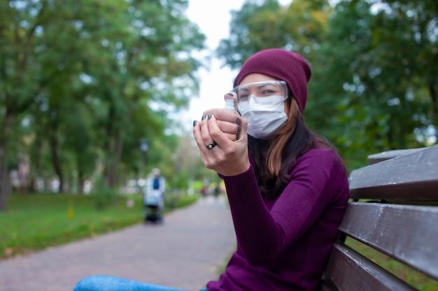 Covid-19 개념입니다. 의료용 마스크와 고글을 쓴 여성이 알코올 젤 소독제로 손을 씻습니다. 코로나바이러스에 대한 보호 및 예방.