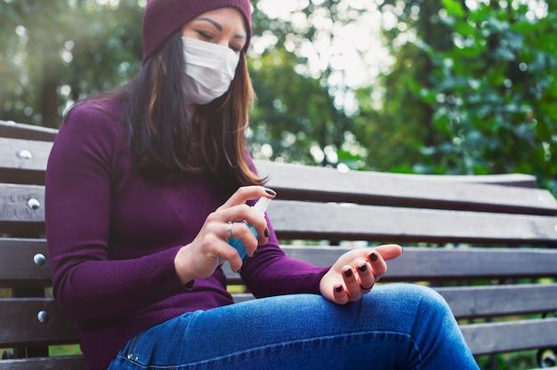 Covid-19 개념입니다. 알코올 젤 소독제로 손을 씻는 의료 마스크를 쓴 여성. 코로나바이러스에 대한 보호 및 예방.