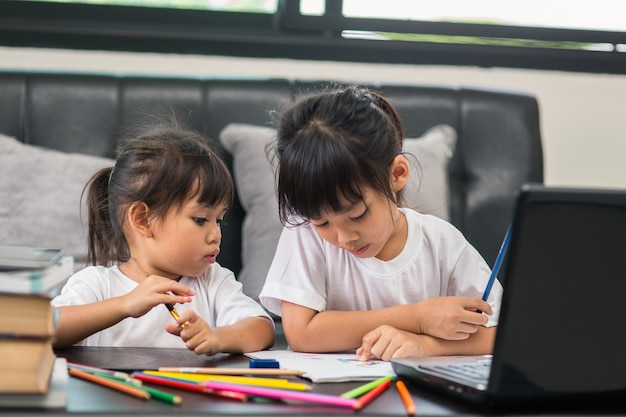Covid-19 коронавирус и обучение из дома, концепция домашнего школьника. маленькие дети изучают онлайн-обучение дома с ноутбуком.
