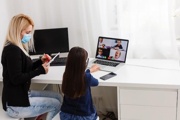 코비드-19 코로나바이러스와 가정에서의 학습, 가정 학교 어린이 개념. 집에서 어머니와 함께 온라인 학습을 하는 어린 소녀. 검역 및 사회적 거리 개념.