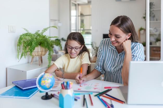 Covid-19コロナウイルスと家庭からの学習、ホームスクールの子供の概念。小さな女の子は母親の助けを借りて勉強します。検疫と社会距離拡大の概念。家庭での学習、オンライン学習。