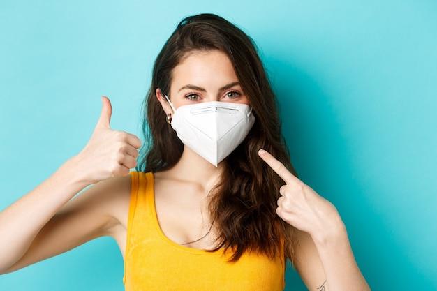 Covid-19、コロナウイルスおよび社会的距離。フェイスマスクを着用してください。顔を指して、親指を上に表示し、青い背景の上に立って、医療レスピレーターで笑顔の女性。