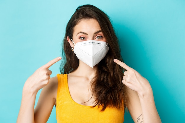 Covid-19、コロナウイルスおよび社会的距離。彼女の顔を指して、パンデミックの間にフェイスマスクを使用するように頼み、青い背景に立って、レスピレーターの若い女性。