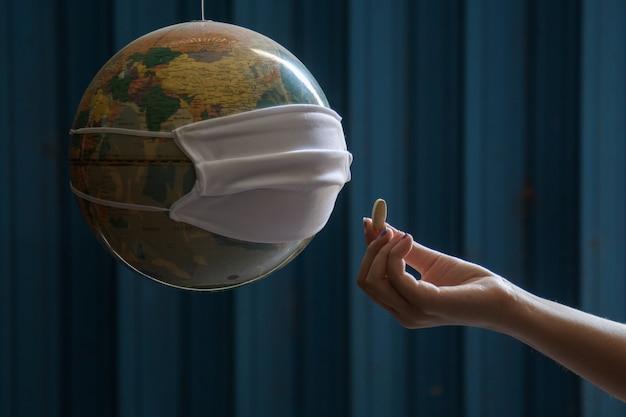 질병을 예방하기 위해 의료용 마스크를 쓴 지구와 함께하는 코비드-19 코로나바이러스 인식 상징 - 세상을 구하고 - 집에 있어