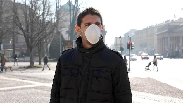 Covid-19 человек на городской улице в защитной маске, защищающей от распространения вируса болезни: coronavirus disease 2019.