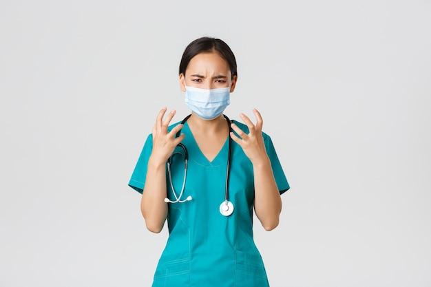 Covid-19、コロナウイルス病、医療従事者の概念。怒って腹を立てているアジアの女性医師、医療用マスクとスクラブの医師、握りこぶしは激怒し、猛烈な白い背景に見えます。
