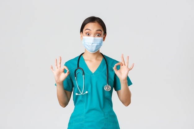 Covid-19、コロナウイルス病、医療従事者の概念。興奮して感動したアジアの女性医師、医療マスクのインターン、承認で大丈夫なジェスチャーを示すスクラブ、白い背景。
