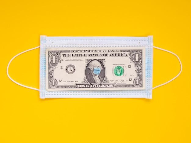 Covid-19 коронавирус в сша, 1 доллар сша с лицевой маской. коронавирус влияет на мировой фондовый рынок. желтый фон