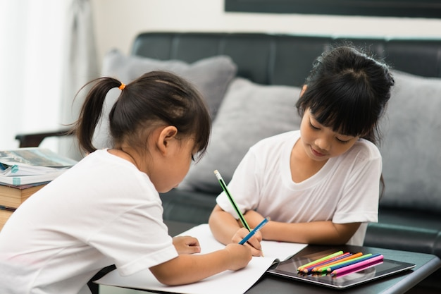 Covid-19 coronavirus and learning from home, home school kid concept. little children study online learning from home with laptop.