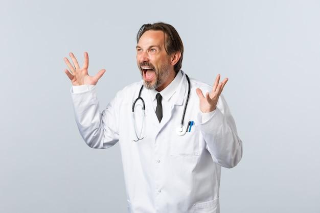 Covid-19、コロナウイルスの発生、医療従事者、パンデミックの概念。白衣を着た狂った狂った医者、クリニックで従業員と対峙し、怒って身振りで示し、激怒しているように見える