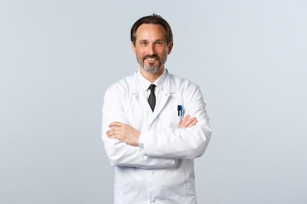 코비드-19, 코로나바이러스 발병, 의료 종사자 및 전염병 개념. 흰 코트를 입은 중년 의사가 팔짱을 끼고, 환자를 도울 준비가 되어 있고, 약을 처방하고, 밝게 웃고 있습니다.