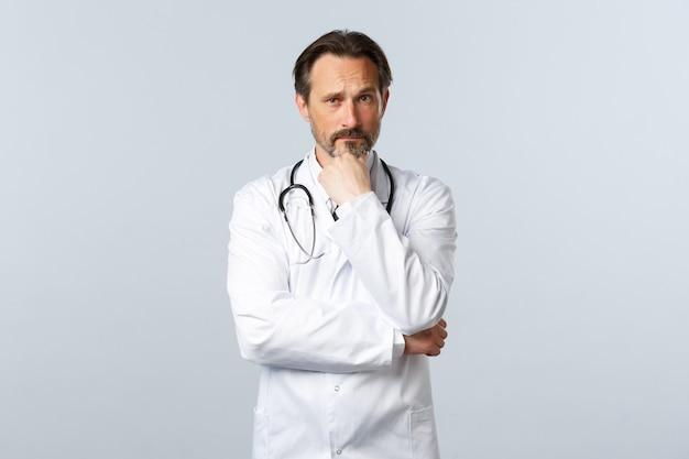 코비드-19, 코로나바이러스 발병, 의료 종사자 및 전염병 개념. 사려깊은 진지한 의사가 결정을 내리고 환자의 경우에 집중하는 모습을 보입니다. 가정하는 의사