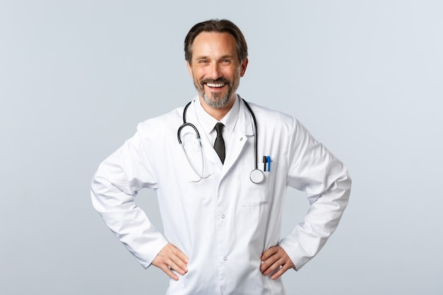 Covid-19, coronavirus outbreak, healthcare workers and pandemic concept. enthusiastic smiling male doctor glad help patients. physician in white coat happy working in clinic or hospital
