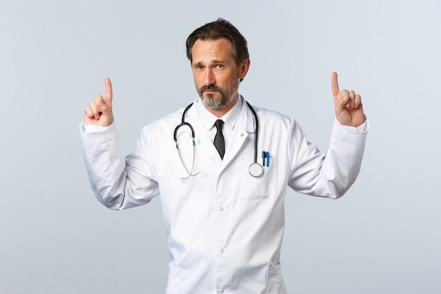 Covid-19, epidemia di coronavirus, operatori sanitari e concetto di pandemia. scettico medico maschio adulto in camice bianco che punta le dita in alto e guarda preoccupato la telecamera, ha dei dubbi