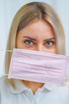 Covid-19 пандемия коронавируса. доктор держит хирургическую розовую маску возле лица. медсестра в защитных халатах в больнице. вселяя уверенность в завтрашнем дне для выхода из кризиса.