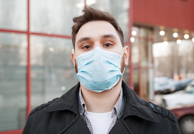 Covid 19コロナウイルス。顔の衛生的なマスクを身に着けている白人の男の肖像
