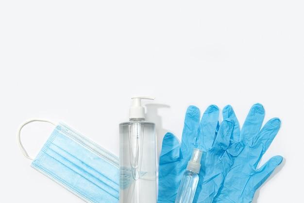 Covid-19コロナウイルスの保護または予防の概念。医療用フェイスマスク、手袋、手指消毒剤、消毒スプレー。上面図。