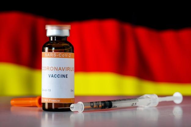 독일 국기의 배경에 주사기에 용량이 있는 코비드 19 코로나바이러스 백신. 독일에서 코로나바이러스에 대한 예방접종 및 예방접종의 개념.