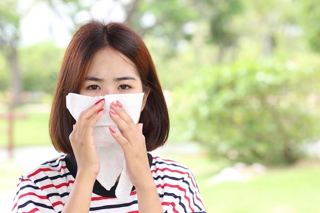 Covid-19(コロナウイルス)、自然の緑の背景、病気、健康概念に風邪を引いた後、彼女の鼻を吹く若い女性