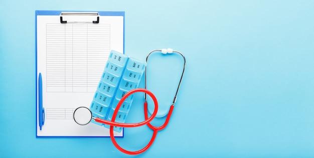 Назначение врача. стетоскоп, таблетки коробки, медицинские документы на рабочем месте врачей в клинике длинный синий баннер. концептуальная медицина, здравоохранение, исследования, наука. форма анализа теста covid-19 coronovirus