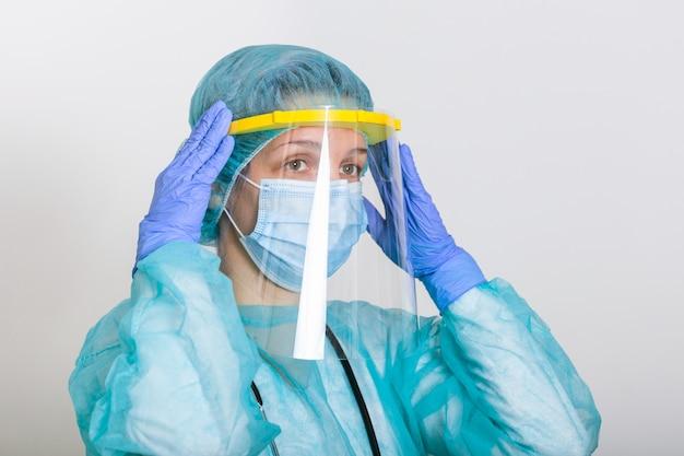 コロナウイルスの発生またはcovid-19、covid-19検疫の概念のためのppeスーツの着用方法を教える医師。