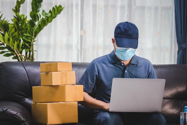 Covid-19中のオンライン配信。オンラインで商品を購入し、危機の際に速達を行う顧客のために、covid-19アジア人男性は自宅で独立して働いています。