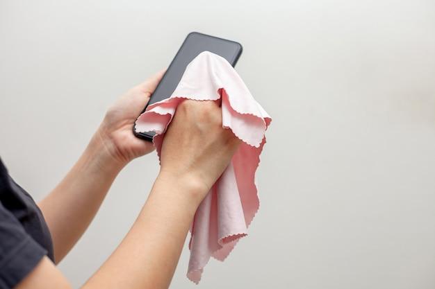 Covid-19疾患予防のための携帯電話のクリーニング。アルコール、安全のためのスマートフォンのワイプの消毒剤、covid-19ウイルスの感染、汚染、細菌、頻繁に触れる細菌。
