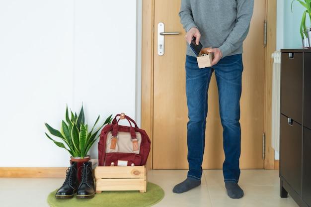 Covid感染を防ぐために家に帰るときに物を箱に入れておく男19。コンセプトcovid-19。コロナウイルス。