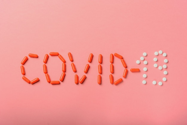 Covid 19 эпидемия гриппа. надпись covid-19 из таблеток, лекарств на розовом фоне, плоская планировка, копия пространства