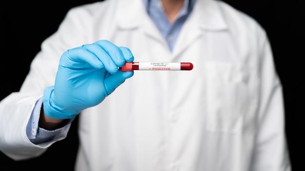 Врач держит в руке коровавирусную вакцину covid 19, зараженный образец крови в пробирке, инъекцию вакцины и шприца. используется для профилактики, иммунизации и лечения от covid-19.