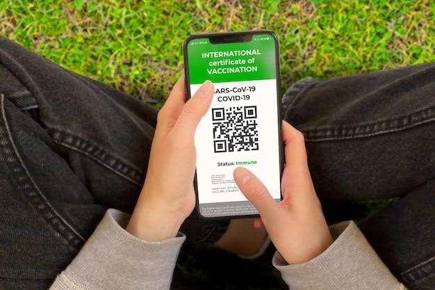 Covid-19: 휴대폰 화면에 디지털 녹색 인증서 또는 covid 디지털 백신 인증서. 어린 소녀는 예방 접종을 받은 디지털 건강 여권으로 스마트폰을 사용합니다.