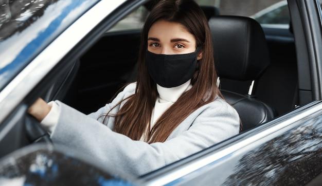 Covid-19. элегантная деловая женщина за рулем на работу в маске для лица