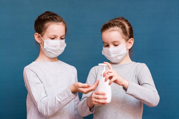 Covid19エピデミック。医療マスクの女の子は青色の背景に消毒剤で手を扱います。