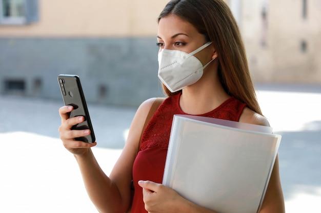 Covid-19世界経済危機携帯電話を使用して仕事を探しているマスクを持つ失業者の女性