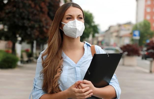 Covid-19 глобальный экономический кризис обеспокоенная безработная девушка в маске ищет работу гуляет по городской улице и составляет биографию