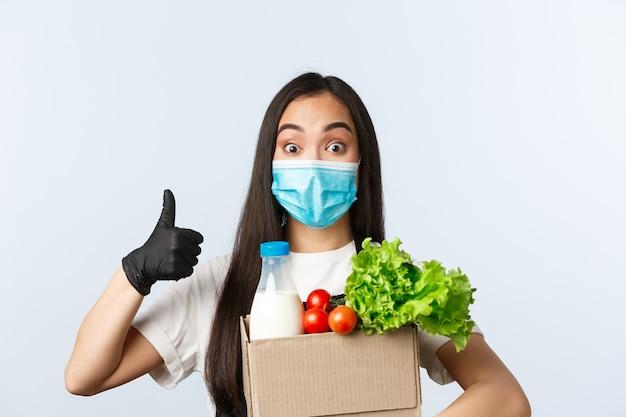 Covid-19, продуктовый магазин, занятость, малый бизнес и концепция предотвращения вирусов. веселая сотрудница магазина, кассир в медицинской маске и перчатках обеспечивает безопасные покупки во время коронавируса, палец вверх