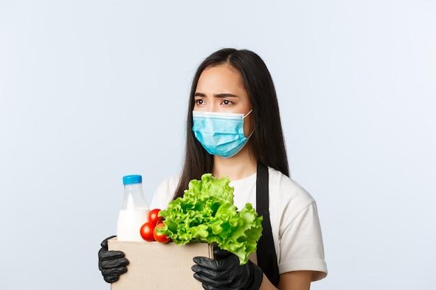 Covid-19、食料品店、雇用、中小企業およびウイルス防止の概念。動揺して悲しいかわいいアジア女性店長、医療マスクのレジ係、食料品注文バッグを保持している手袋