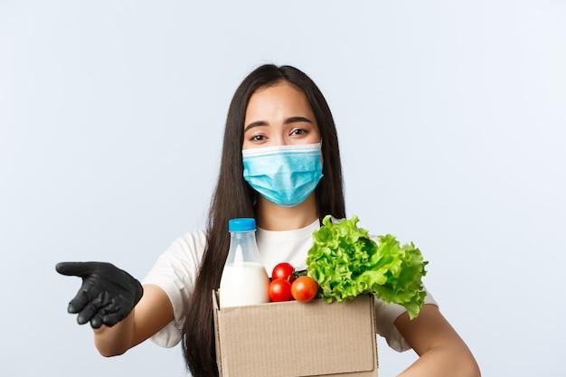 Covid-19, продуктовый магазин, занятость, малый бизнес и концепция вирусов. милый молодой азиатский работник магазина, кассир в медицинской маске и перчатках ждет денег для заказа, держа упакованные продукты.