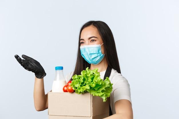 Covid-19, продуктовый магазин, занятость, малый бизнес и концепция вирусов. улыбающийся кассир, азиатский работник магазина в медицинской маске протягивает руку, чтобы не платить наличными, держа заказ на упакованные продукты.