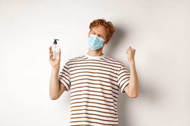 Covid-19、健康とライフスタイルのコンセプト。赤い髪のハンサムな若い男は、フェイスマスクを着用し、祝って、手の消毒剤を示し、陽気な白い背景を探しています。