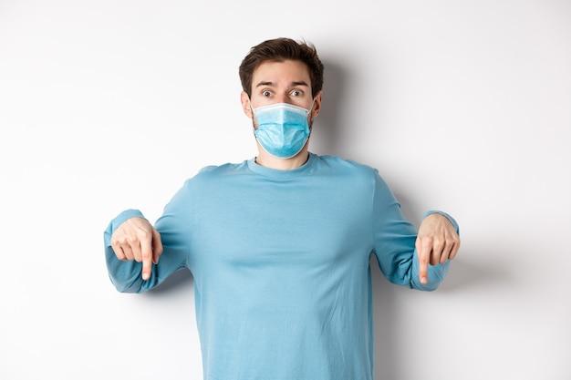 Covid-19, 건강 및 검역 개념. 프로모션 로고를 확인하고 손가락을 아래로 가리키고 코로나 바이러스, 흰색 배경에서 의료 마스크를 쓰고 놀란 남자.