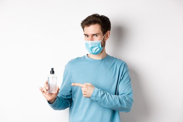 Covid-19、健康と検疫の概念。医療マスクの白人男性が手指消毒剤でボトルに人差し指、消毒剤をお勧めし、白い背景の上に立っています。