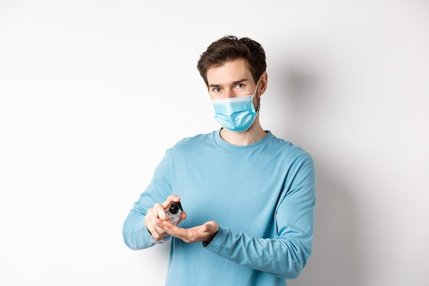 Covid-19、健康と検疫の概念。手指消毒剤を使用して医療マスクの白人男性、コロナウイルススプレッド、白い背景から消毒剤を適用します。