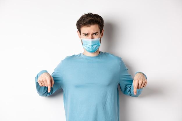 Covid-19、健康と検疫の概念。悲しい男が不平を言ってがっかりしているように見え、ロゴを指で下に向け、コロナウイルスのパンデミックから医療用マスクに立っています。