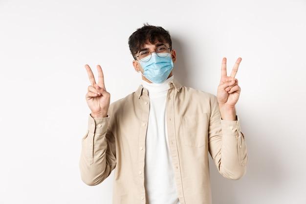 Covid-19, концепция здоровья и реальных людей. симпатичный счастливый парень в медицинской маске, оставаясь позитивным, показывая знаки мира и улыбаясь, стоя на белой стене.