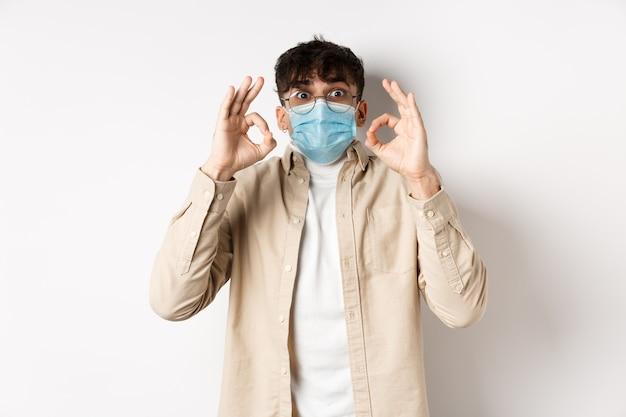 Covid-19, концепция здоровья и реальных людей. взволнованный и впечатленный парень в стерильной маске для лица показывает одобрительные знаки ок, хвалит классную вещь, забавляясь, стоя на белой стене.
